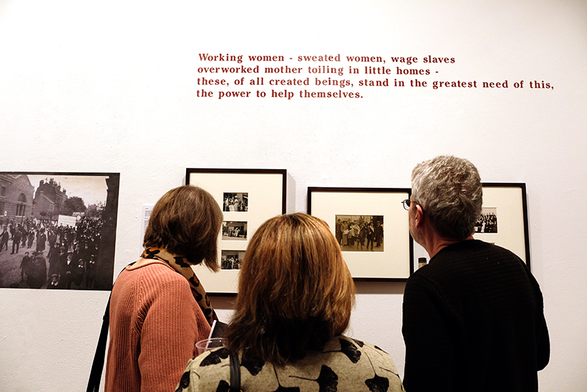 Three people standing in a gallery looking at framed black and white photographs.