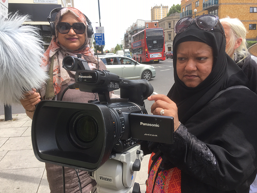 Two women in headscarves stand in the street holding a film camera and boom mic.